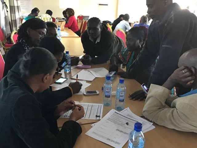 A quality improvement team at work around a table in Kenya